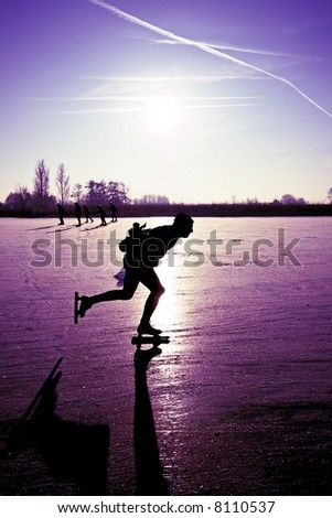 Ice skating with a beautiful purple sunset in the countryside of the Netherlands - stock photo