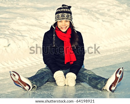 Ice skating woman sitting on the ice smiling. - stock photo