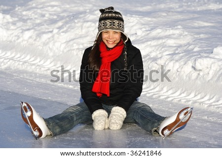 Ice skating. Young woman sitting on the ice, while skating outside on a sunny winter day in Quebec City. - stock photo