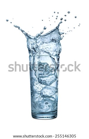 ice splashes into glass of water - stock photo