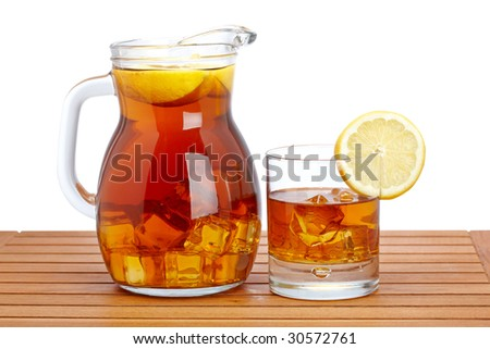 Ice tea pitcher and glasss with lemon and icecubes on wooden background. Shallow depth of field - stock photo