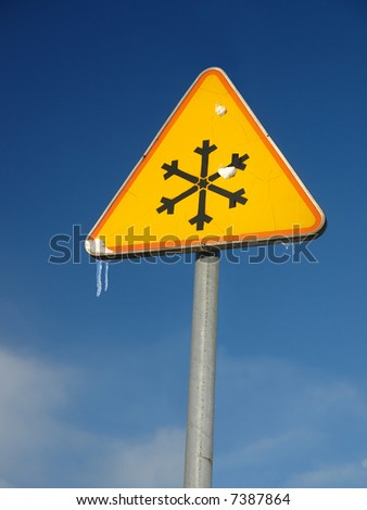 Ice warning roadsign over blue sky - stock photo