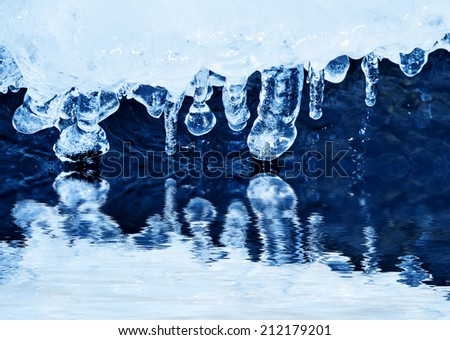 ice with icicles and a river water - stock photo