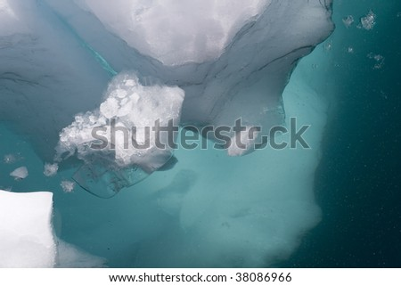 Iceberg above and below the water surface. Clear turquoise colors.
