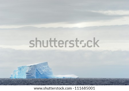 Iceberg floating in ocean - stock photo