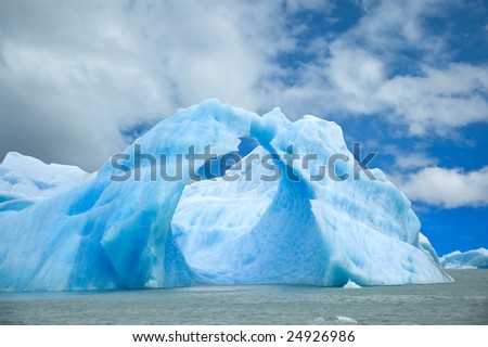 Iceberg floating in the water forming an arch. - stock photo