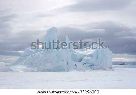 Iceberg frozen solid in the sea ice of Antarctica - stock photo