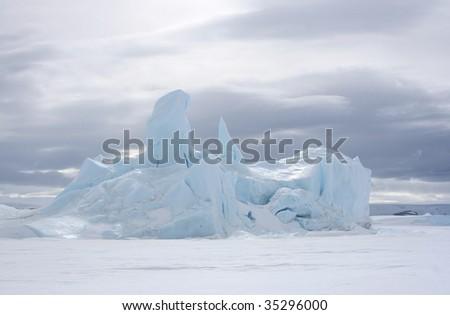 Iceberg frozen solid in the sea ice of Antarctica - stock photo