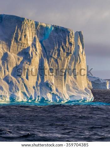 Iceberg in Antarctic ocean at sunset - stock photo