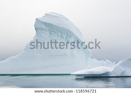 Iceberg in Antarctic waters on a cloudy summer day. - stock photo