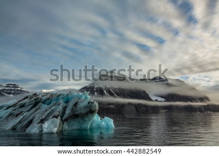 Iceberg in Greenland.  An iceberg or ice mountain is a large piece of freshwater ice that has broken off a glacier or an ice shelf and is floating freely in open water, heading out to sea. - stock photo