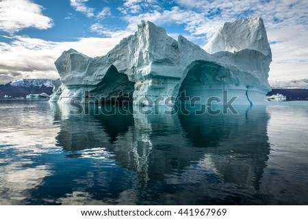 Iceberg in Greenland. No two icebergs are alike, and when you see an iceberg for the first time, you may be seeing shapes and sizes that no-one has seen before. This iceberg has several ice caves. - stock photo