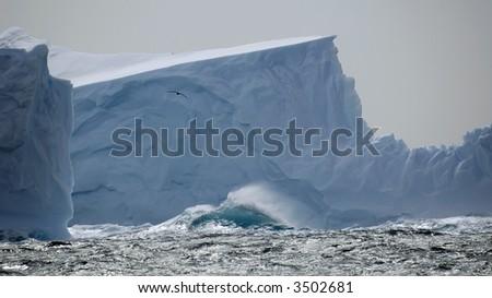 Iceberg in stormy seas - stock photo
