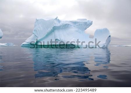 Iceberg reflection in calm ocean - stock photo