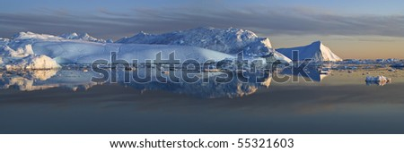 Iceberg wall seen from a little distance. Sunset. There are smaller pieces of ice in the foreground. - stock photo
