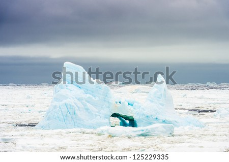 Iceberg with a hole of Antarctica. Antarctic region of the Southern Hemisphere, almost entirely south of the Antarctic Circle, and is surrounded by the Southern Ocean. - stock photo
