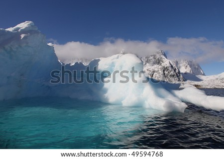 Iceberg with pool in Antarctica seen from a sailing boat - stock photo