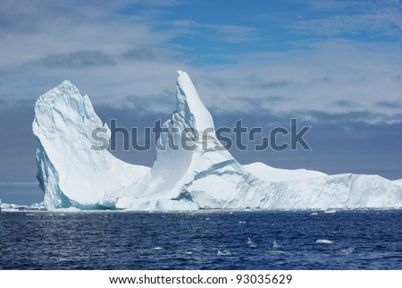 Iceberg with two vertices floating in the ocean. - stock photo