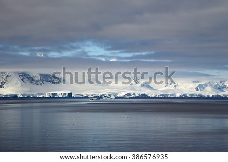 Icebergs and snow covered mountains in the Gerlache Strait (Antarctic Peninsula) - stock photo