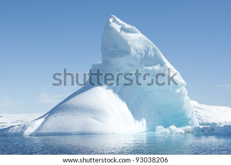 Icebergs in the sunny bright light on the background of the island. - stock photo