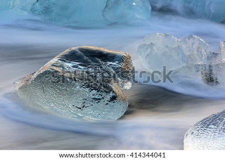 Icebergs near the black volcanic beach during sunset in wintertime with a long exposure time - stock photo