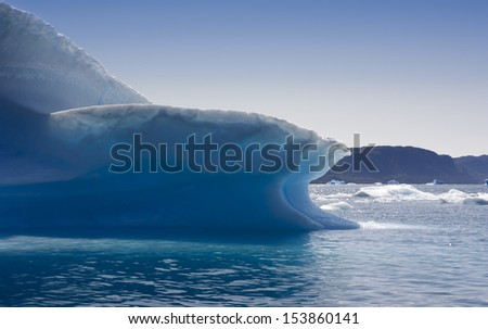 Icebergs of Greenland at a short distance. Huge masses of thawing ice. Deep-water fjords of Greenland. - stock photo