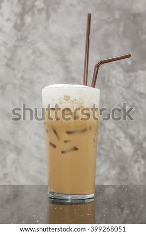 Iced cappuccino coffee topped with fresh milk layer on blurred gray wall background. - stock photo
