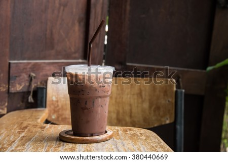 Iced chocolate on student desk - stock photo
