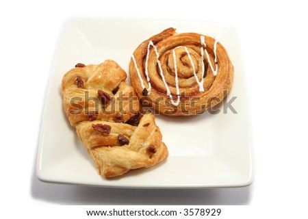 iced cinnamon swirl and a maple and pecan danish pastry on a square white plate - stock photo