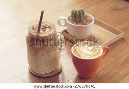 iced coffee and cappuccino latte art with cactus in coffee shop vintage color tone - stock photo