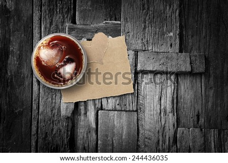 Iced coffee and torn paper on wood floor, background for valentine's day. - stock photo