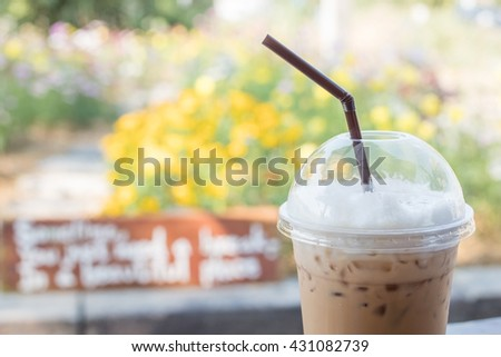 Iced coffee cappuccino in plastic cup with straw on flower garden blurred background - stock photo