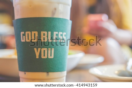 Iced coffee god bless you with milk is on the table.Vintage filter. - stock photo