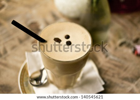 Iced  coffee in a glass with coffee beans and black straw in a cafe. - stock photo
