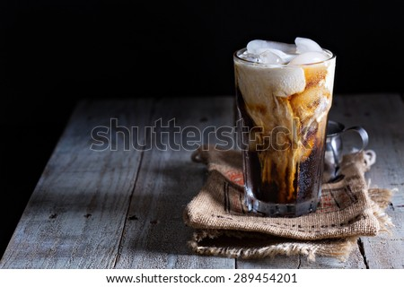 Iced coffee in a tall glass with cream poured over - stock photo
