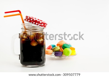 Iced Coffee in bottle with macaroons, white background