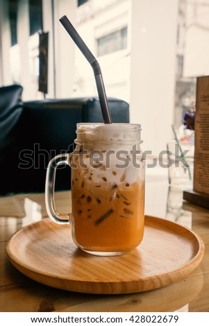 Iced coffee in coffee shop on wooden background, Selective focus, Film simulation - stock photo