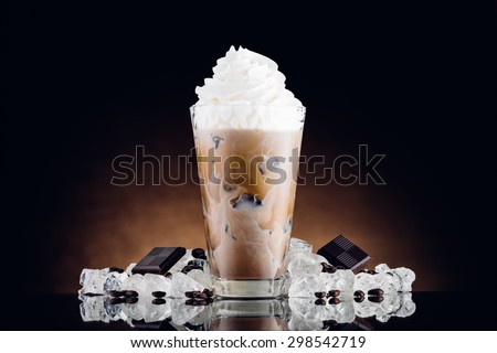 Iced coffee in glass and crushed ice on brown background - stock photo