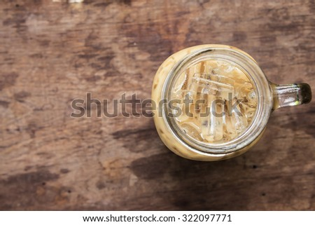 iced coffee in jar on wood background top view