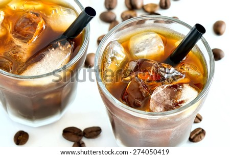 Iced coffee in two glasses with black straws and coffee beans on the backstage - stock photo