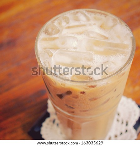 Iced coffee on wooden table with retro filter effect - stock photo