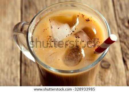 Iced coffee with cinnamon in glass over rustic wooden background - stock photo