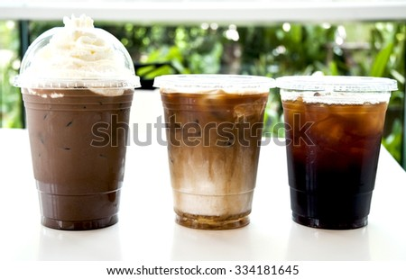 Iced coffee with cream in take away cup on white background .Collection of iced coffee on white table  - stock photo