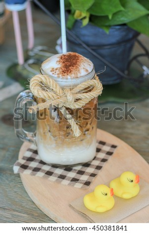 Iced coffee with milk in glass on wooden table
