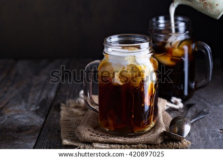 Iced coffee with milk in mason jars  on the table - stock photo