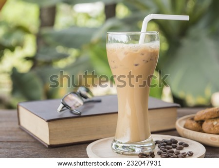 Iced coffee with milk is placed on a wooden table - stock photo