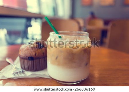 Iced coffee with milk on wood table made with Vintage Tones - stock photo