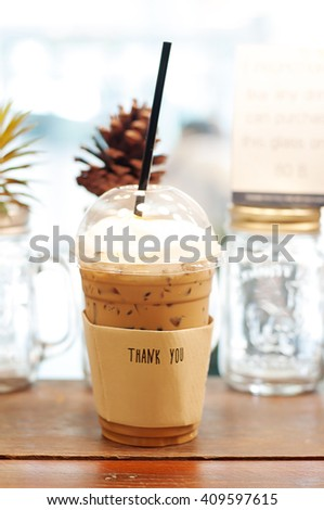 ICED COFFEE WITH STRAW IN PLASTIC CUP WITH THANK YOU WORD ON PAPER COFFEE CUP SLEEVE, SELECTIVE FOCUS AND BLURRY BACKGROUND, BLANK COPY-SPACE - stock photo