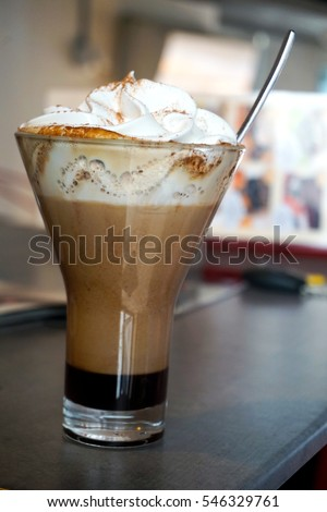 Iced coffee with whipped cream on wooden table at cafe
