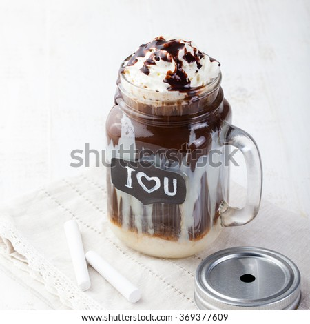 Iced cold coffee, frapuccino with whipped cream and chocolate syrup in jar with chalkboard * I Love You * on a white table    - stock photo